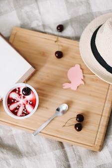 チェリーアイスクリームの本と麦わら帽子の上面図と夏の構成