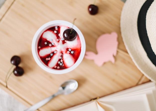 桜のアイスクリームの本と麦わら帽子の上面図と夏の構成