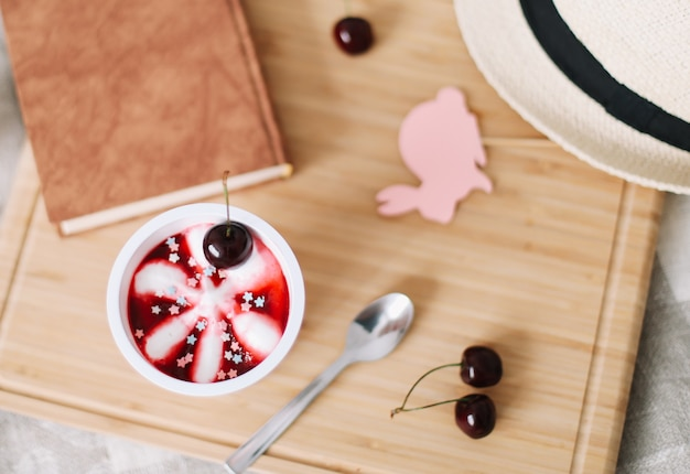 Summer composition with cherry ice cream book and straw hat top view
