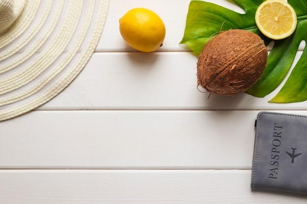 Summer composition with coconut, lemon, monstera leaf hat and passport on a white wooden table