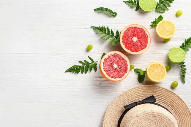 흰색 나무 테이블에 모자와 열대 과일 여름 구성