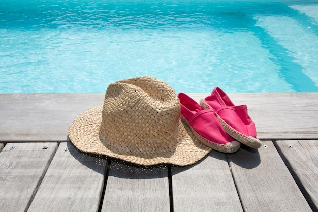 Summer composition with hat shoes on the wooden deck and pool