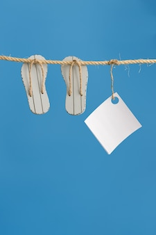 Summer composition with marine items hanging on string with blue colored background