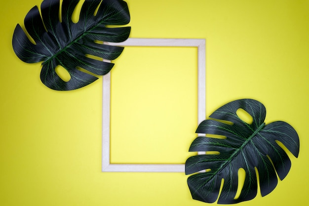 Summer composition with monstera leaves and frame tropical leaves, empty photo frame on pastel yellow background.