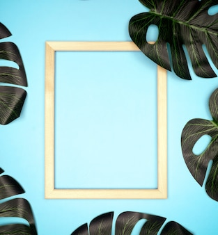 Summer composition with monstera leaves and frame