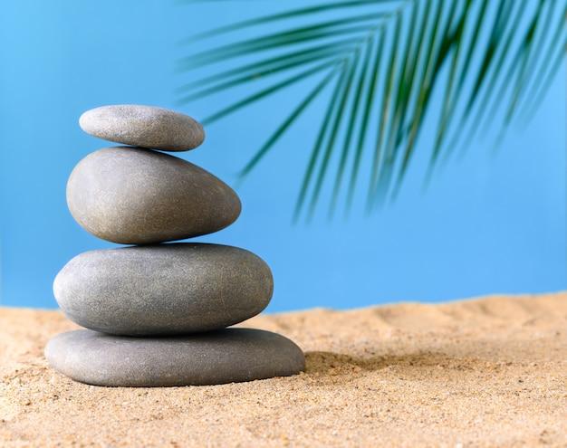 파란색 배경에 모래에 자연석이 있는 여름 구성