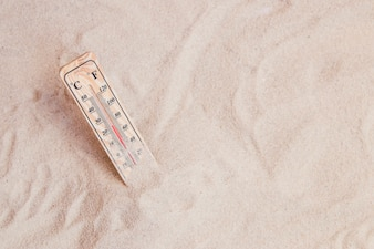 Summer composition with sand and thermometer