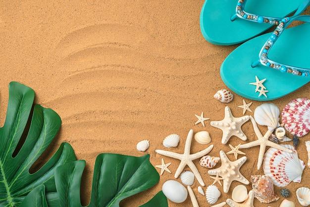 貝殻、ビーチサンダル、砂の上のモンステラの葉を使った夏の作曲。上面図、水平。