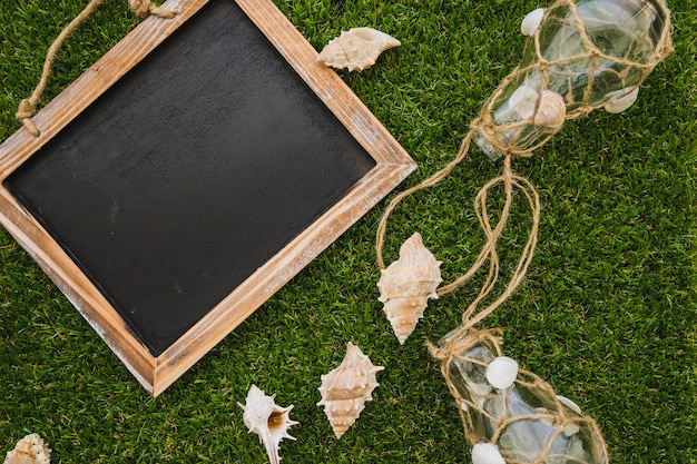 Summer composition with slate, seashells and light bulbs