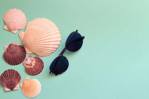 Летняя композиция с солнцезащитными очками и ракушками из японских морских гребешков