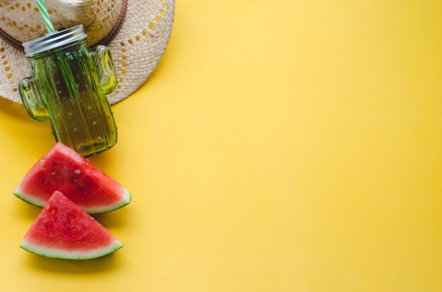 Summer composition with watermelon, hat and container for juices on yellow background. concept of summer. copy space. flat lay.