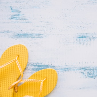 Summer composition with yellow flip flops