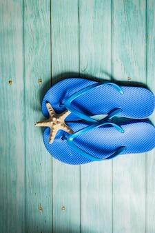夏のコンセプト-青い木の床に青いビーチスリッパ。上面図