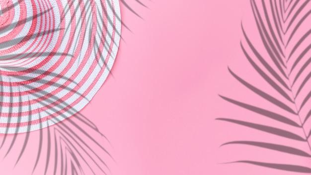 夏のコンセプトフラットレイ、テキスト用の空のスペースとピンクのパステルカラーの背景に帽子の夏のヤシの影の葉の反射。旅行休暇のコンセプト。