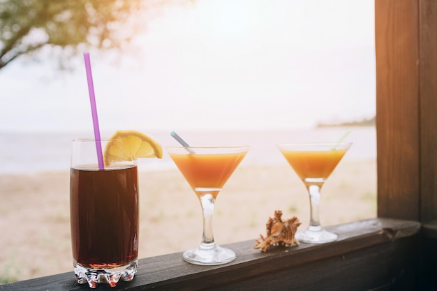 Summer concept: fresh exotic cocktails on wooden edge. shell lying between glasses. cola with straw and lemon. island life. paradise.