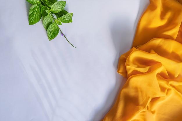 夏のコンセプト。白い紙の背景に緑の葉とシダ黄色のスカーフ。