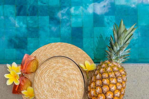 夏のコンセプト帽子グラスパイナップルの花プールサイド