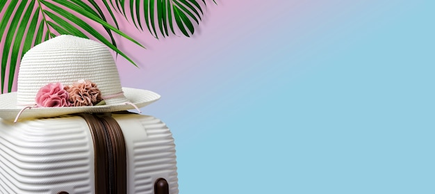 Summer concept of hat on luggage and tropical leaves with copy space