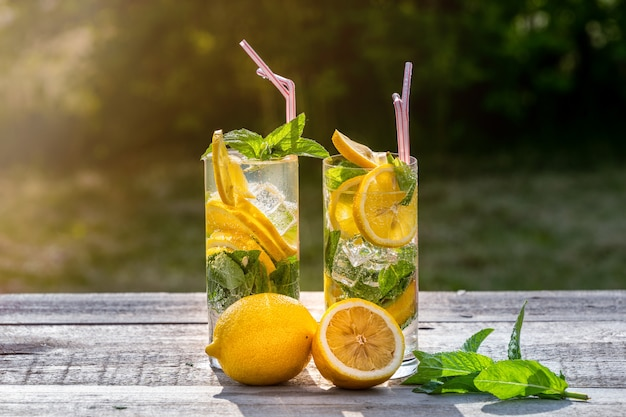 Summer concept. homemade lemonade with lemon, mint and ice in glasses, on old wooden table, outdoor.