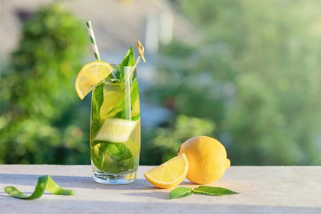 夏のコンセプトです。レモネードまたはモヒートカクテル、レモン、キュウリ、ミント、冷たいさわやかなドリンクまたはドリンク、屋外。氷と紙のストローで冷たいデトックス水、コピースペース。