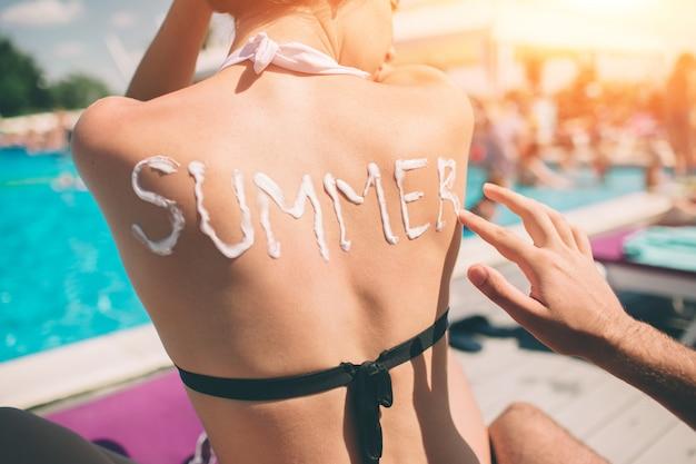 夏のコンセプトです。女性の背中に「夏」という言葉を書いている男性。女の子の肌に日焼け止めを適用する男。