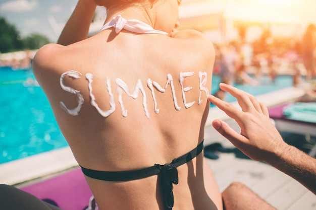 Summer concept. man writing the word summer on a woman's back. man applying sunscreen on the skin of a girl.
