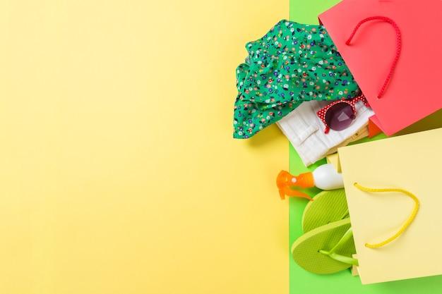 洋服がいっぱいのカラフルなショッピングバッグの夏のコンセプト。 tシャツ、デニムショートパンツ、ビーチサンダル、日焼け止めのボトルが入ったギフトバッグ。夏のウィッシュリストのコンセプト。黄色の背景に上面図のコピースペース。