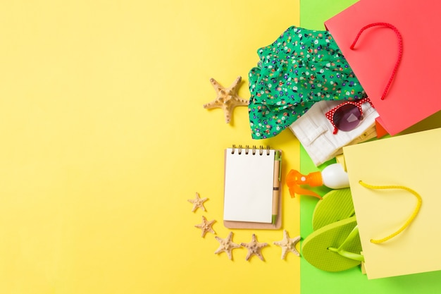 洋服がいっぱいのカラフルなショッピングバッグの夏のコンセプト。 tシャツ、デニムショートパンツ、ビーチサンダル、ノートブック、日焼け止めのボトルが入ったギフトバッグ。黄色の背景に上面図のコピースペース。
