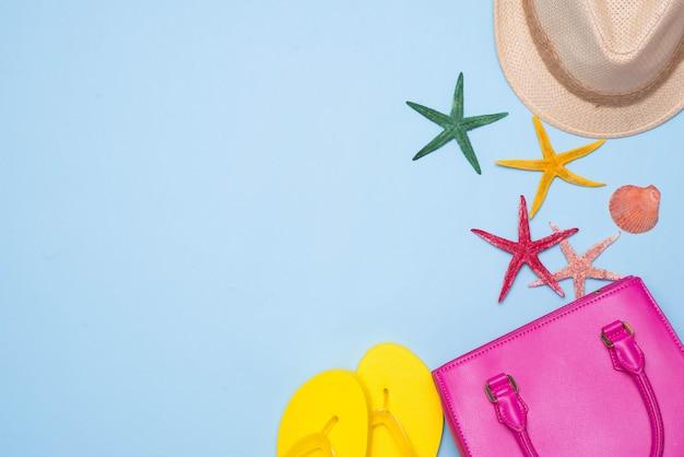 夏のコンセプト。水色の背景にアクセサリーとピンクのハンドバッグ