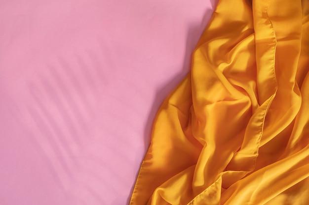 夏のコンセプト。簡単な赤い紙の背景にシダの葉と黄色のスカーフの影。