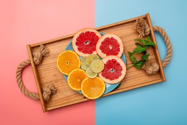夏のコンセプトは、ピンクと青の背景に木製トレイにグレープフルーツ、オレンジ、レモンをスライスしました