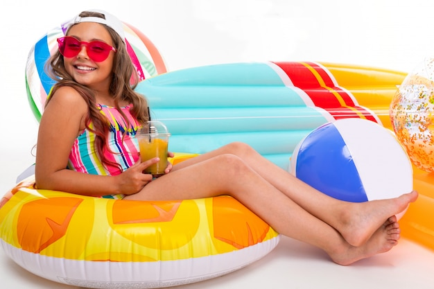 Summer concept, tanned girl sitting around air mattresses, circles and swimming balls