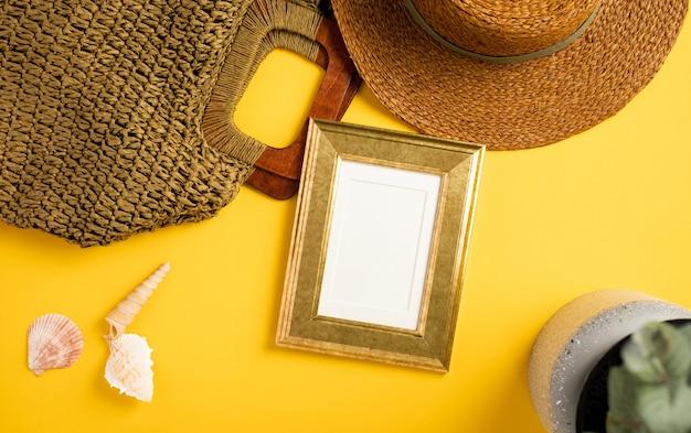 여름 컨셉입니다. 선명한 노란색 배경에 밀짚 모자, 조개, 가방이 있는 상위 뷰 황금 그림 프레임 모형
