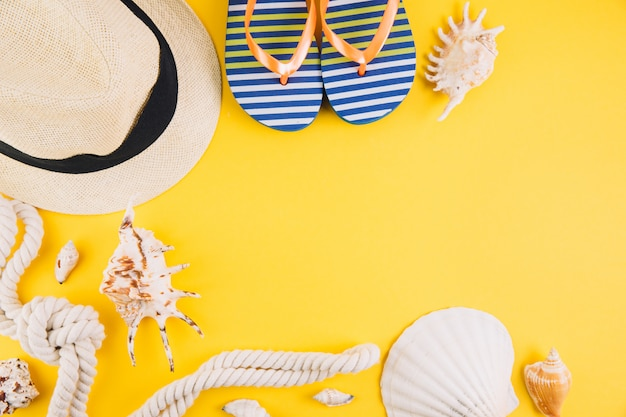 Summer concept. travel accessories: a straw hat, a camera, a rope, shells and slippers.