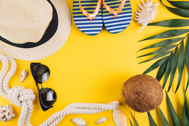 Summer concept. travel accessories: a straw hat, a coconut, a rope shells, slippers and sunglasses.