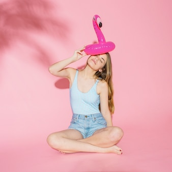 Summer concept with girl and inflatable flamingo