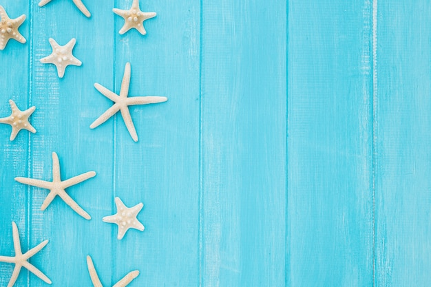 Summer concept with starfish on a blue wooden background with copy space
