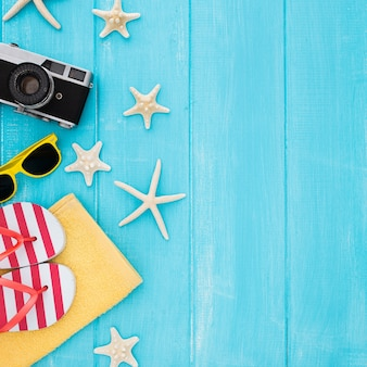 Summer concept with vintage camera, sunglasses, towel, starfish on blue wooden background