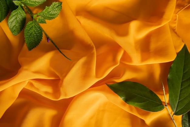夏のコンセプト。黄色のスカーフ生地のテクスチャの背景と緑の葉。
