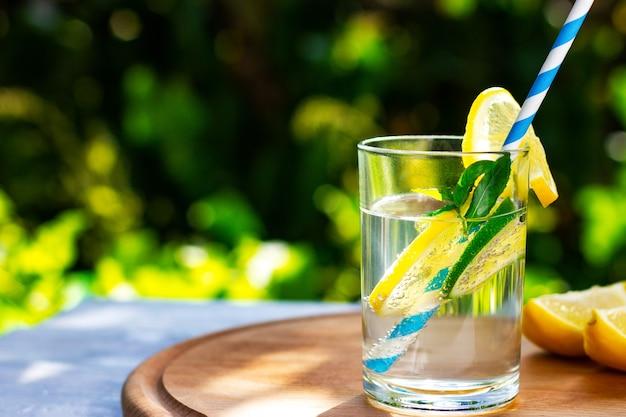 ストローで夏の涼しいレモンとライムの飲み物