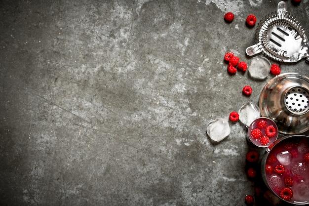 氷と野生のラズベリーの夏の冷却カクテル。石のテーブルの上。