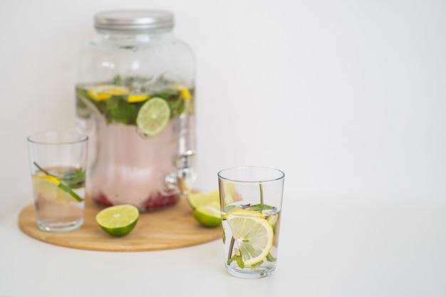 Летний прохладительный напиток с ягодами и цитрусовым лимонадом в многоразовой стеклянной бутылке и стаканах homemad ...