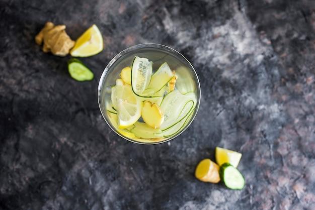 신선한 오이, 레몬, 생강을 곁들인 여름 냉각 음료. 아름다운 잔에 마신다. 어두운 배경에 여름 음료 프리미엄 사진