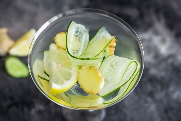 Летний прохладительный напиток со свежим огурцом, лимоном и имбирем. пейте в красивом стакане. летний напиток на темном фоне