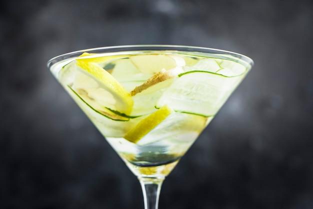 신선한 오이, 레몬, 생강을 곁들인 여름 냉각 음료. 아름다운 잔에 마신다. 어두운 배경에 여름 음료