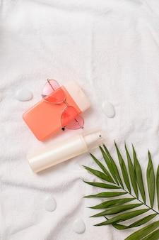 Летний косметический крем и спрей с солнечно-розовыми очками в форме сердца и пальмового листа на белом полотенце