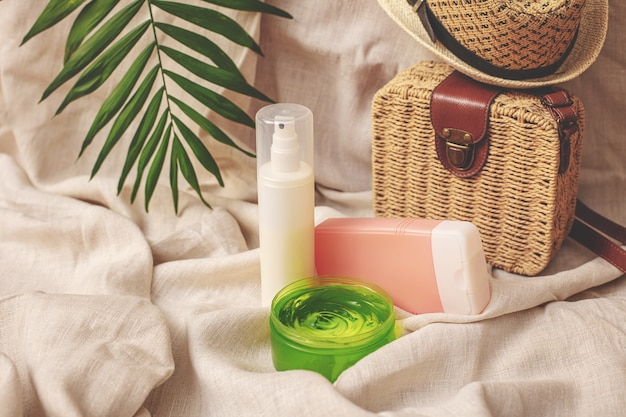 Summer cosmetics creams and gels with a straw hat handbag and palm leaf on the background of linen fabric