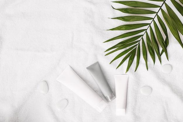 Набор летней косметики из кремов белые камни и пальмовый лист на белом полотенце