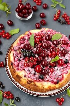 딸기와 여름 별장 치즈 케이크는 어두운 표면, 세로 사진, 근접에 있습니다