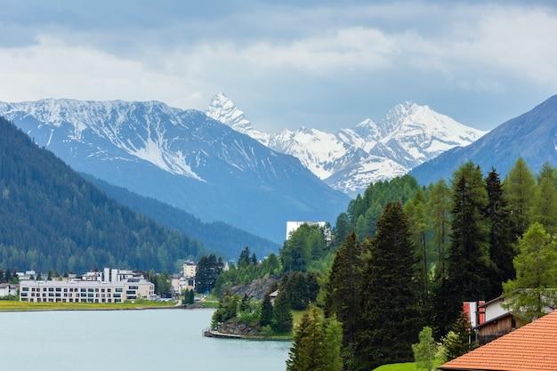 ダボス湖、町の郊外、遠くに雪が降る山々のある夏の田舎の風景(スイス)